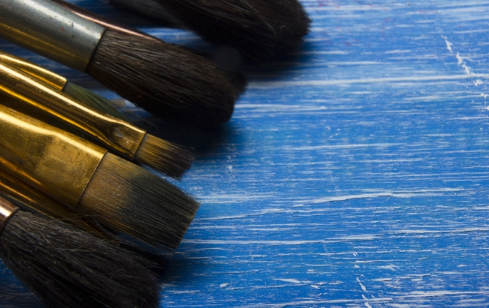 Painting tools colour palette and Artist paint brushes on abstract artistic background.